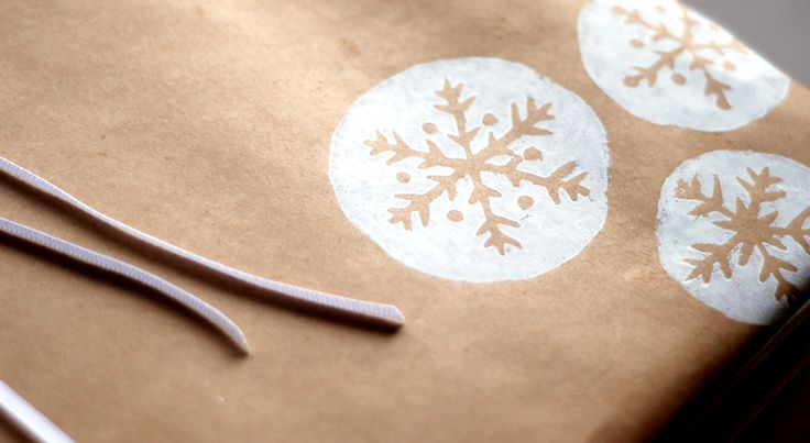 Christmas gift wrap made using a snowflake lino cut and water based block printing ink.