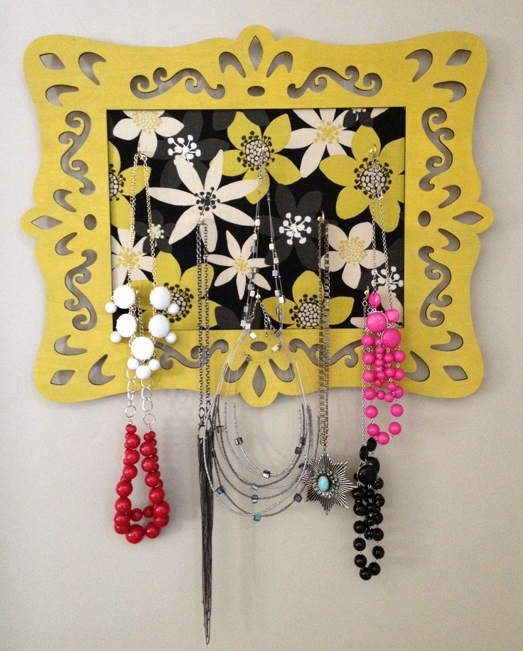 """I wanted a necklace hanger so I made this one. I got a laser cut frame (then painted it), a piece of plywood (for the middle), some fabric, hooks (8 on the board), and a hanger for the back. So simple and love how it dresses up the wall and holds my necklaces. It's 22"""" wide x 17 1/2"""" high"""