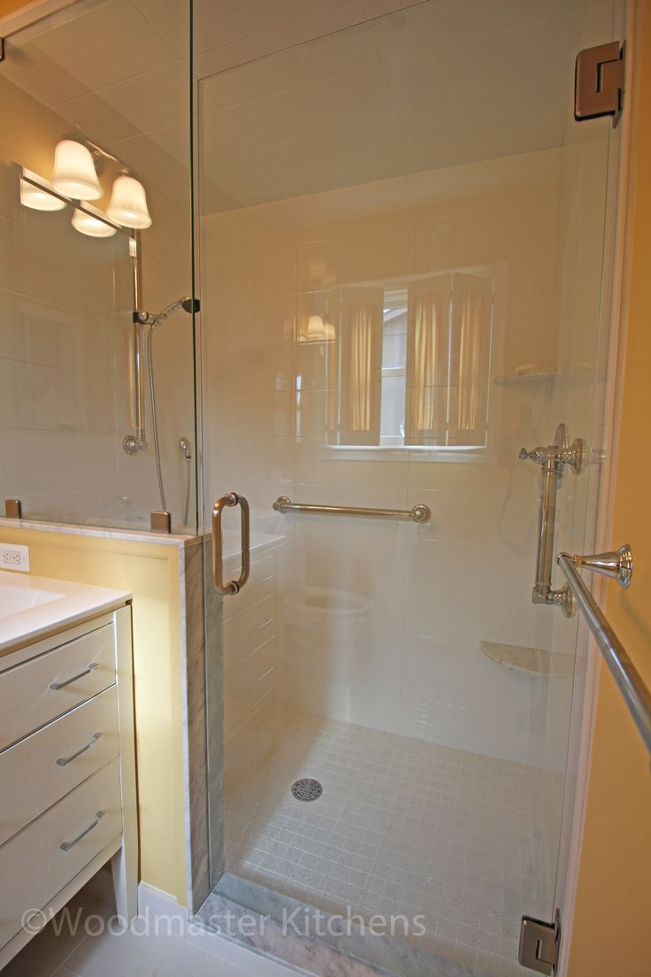 This eclectic master bathroom design packs a lot of features into the space.  The large, walk-in shower with a Euro style glass door and panel is the focal point of the bathroom and includes grab bars, an adjustable slide bar with handheld showerhead, and corner storage shelves.  The free standing vanity cabinet incorporates a porcelain top and integrated bowl.  A recessed medicine cabinet with a mirrored front finishes off this bathroom.