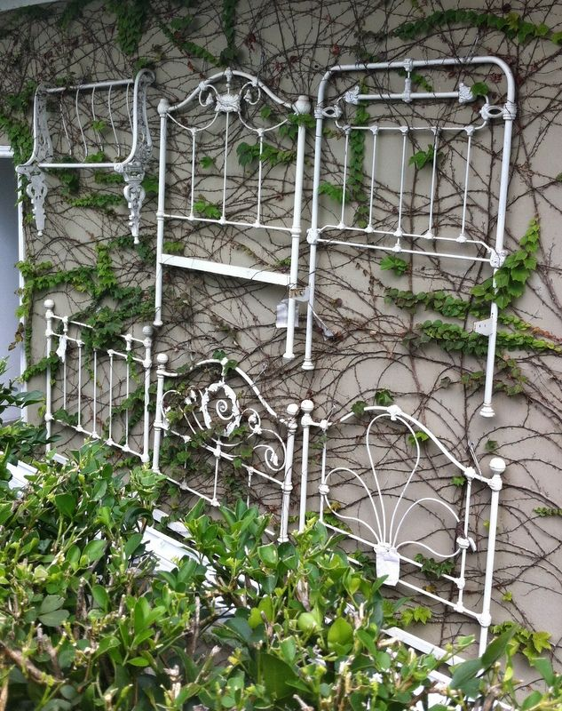 Old metal headboards used as trellis/garden wall art.