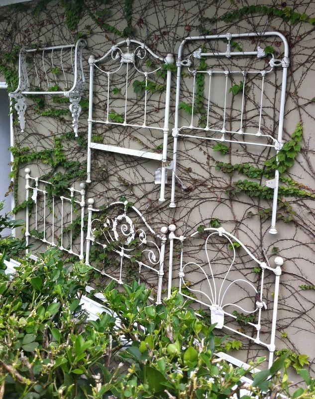 Old metal headboards used as trellis/garden wall art.