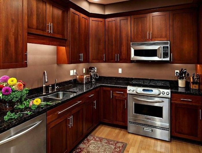 cherry wood kitchen cabinets with silver appliances and black countertops