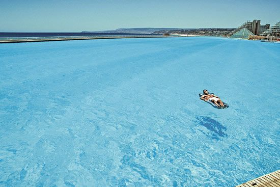 No jellyfish, sharks, or seaweed. World's largest swimming pool -- in Chile. 1013 meters long. Covers 80 acres. Its deepest end reaches 115ft and it holds 66 million gallons of water... i want to go here!!