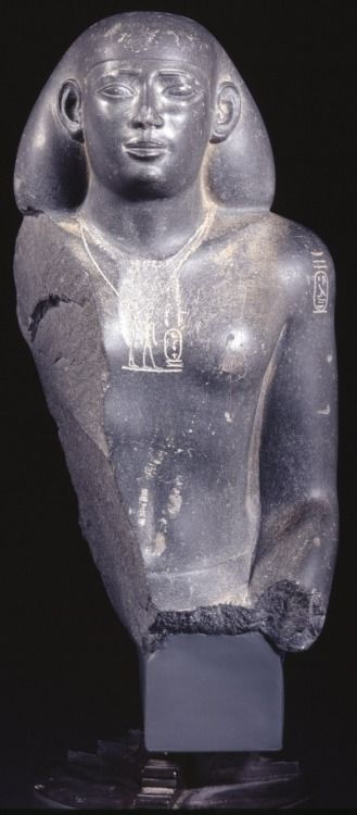 Statue 26th Dynasty Head and right side of the body of a basalt male figure: wearing a bag-wig and a pectoral depicting the goddess Neith and Psamtek II, named by the cartouches. The original pectoral, presumably naming an earlier pharaoh, has been erased. The nomen of Psamtek II is also on the right shoulder, and there are three columns of Hieroglyphic text on the back-pillar. (Source: The British Museum)