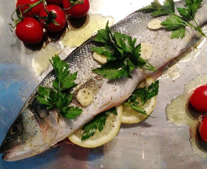Een van de makkelijkste manieren om zeebaars te bereiden: zeebaars met citroen, knoflook, peterselie en olijfolie uit de oven.
