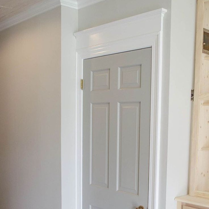 Adding height to doors with additional trim on top. The wall color is Sherwin Williams Agreeable Gray, door color is Sherwin Williams Pussywillow.