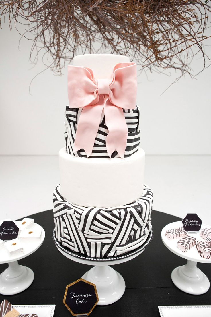 Super cute black and white wedding cake with pink bow.  Photo by Perez Photography. www.wedsociety.com  #wedding #cakes