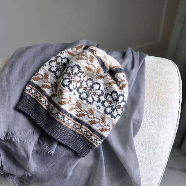 English roses and ivy meander around the crown of Sheila Joynes's chic topper. Stitched in the round from the corrugated rib band up, this is a terrific first fair Isle project for an otherwise experienced knitter.