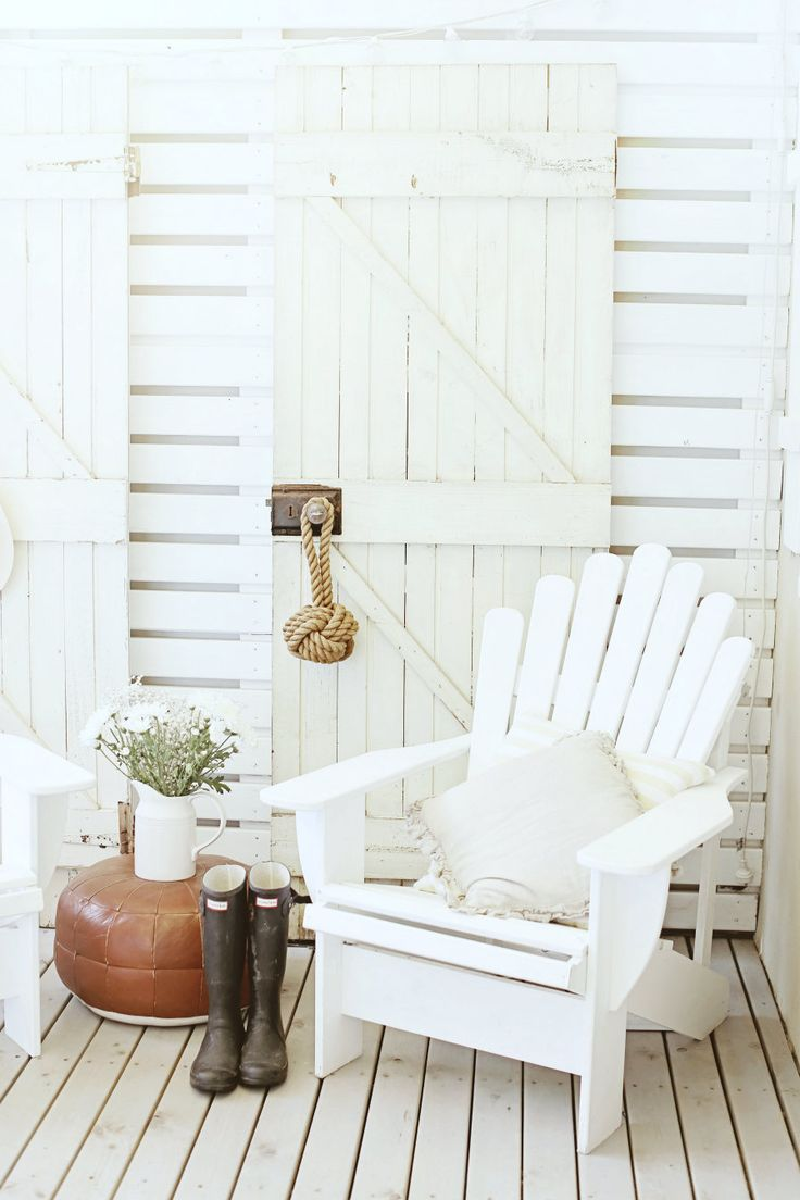 A Beach Cottage look with an old rustic door and an adirondack chair in all white.