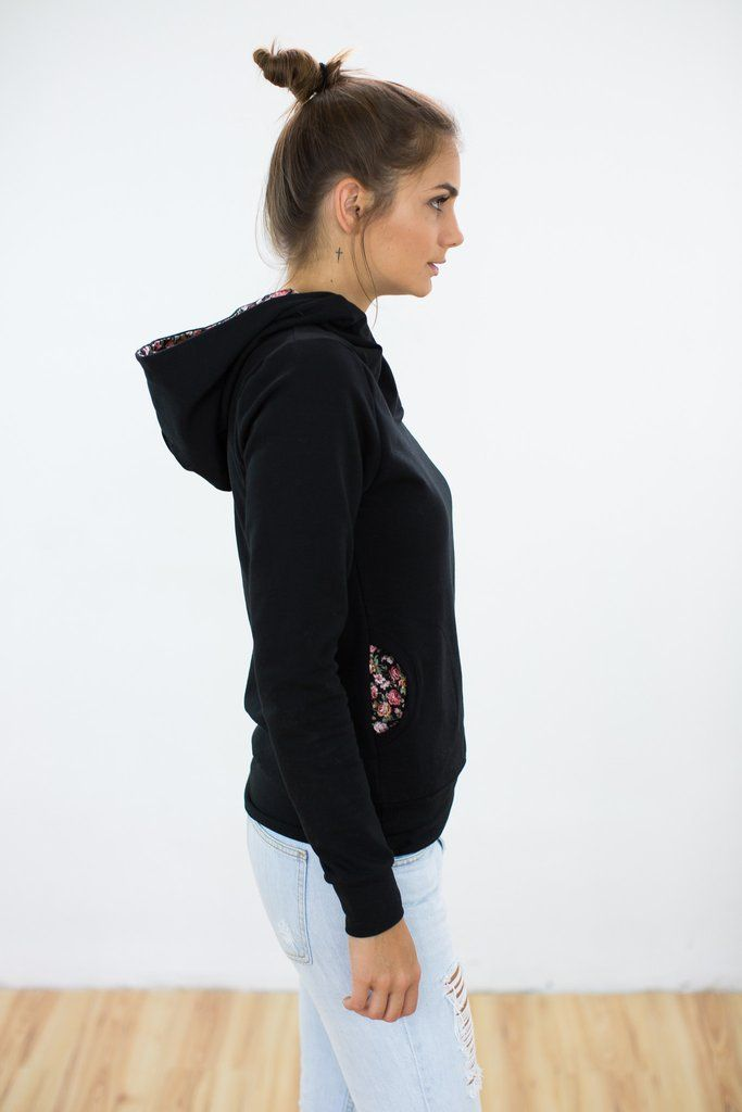 Hoodie L'Amour Black This ultra cosy black hoodie will be the first thing you reach for when you're rushing out the door. The crossed neckline, with pretty floral rose lining will keep you nice and warm, while the side pockets, with the same floral lining, give this hoodie a more casual touch. Plus, it requires little to no effort, simply pair it with skinny jeans and booties and you'll be out the door in no time! A large, black and white polka dot print button decorates the neckline.