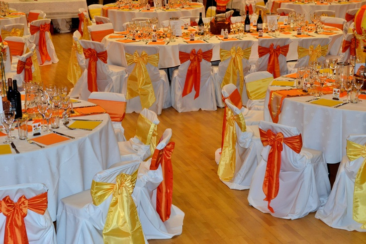 Alternating Orange and Yellow Satin Bows on White Chair Covers