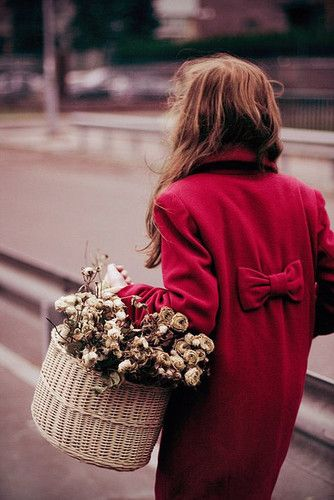 Red coat with red bow in back above waist, woman carrying white wicker basket with white flowers