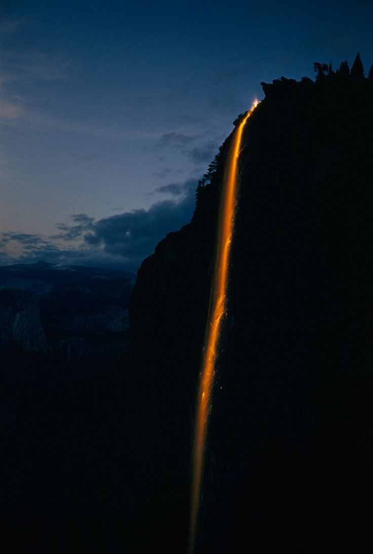 A bright orange river of sparks cascades from a high cliff in Yosemite National Park, May 1958. Photograph by J. Baylor Roberts, National Geographic