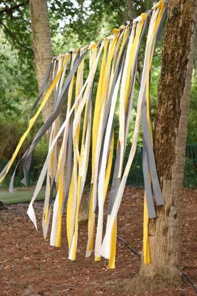 Yellow, white, and titanium colors paper streamers for a makeshift background at an outdoor wedding.