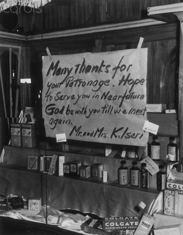 WWII - Little Tokyo, Los Angeles, CA: A sign left taped to a chemist shop by a Japanese American couple Mr. and Mrs. Kilseri. They, along with many other Japanese Americans, were forced to move to an internment camp during the war.