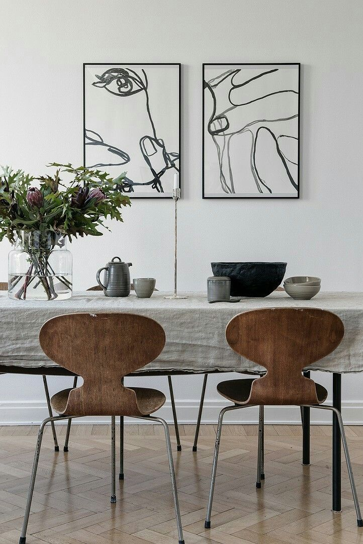 Monochrome dining room with wall line drawing art, wood chairs, chevron floors
