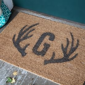 Make this stenciled monogram and antler door mat from an Ikea coir rug.