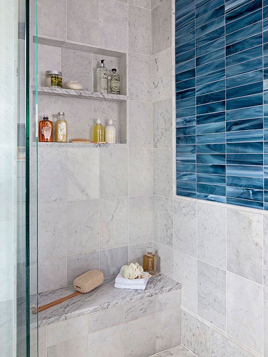 Keep busyness at bay by devising a walk-in shower seat that treads softly into view. This marble-tile bench, handily set beneath a pair of toiletry niches, takes a back seat to vivid blue tiles inset in the adjacent wall. A solid marble top finely distinguishes the bench from the like-color tiled backdrop./