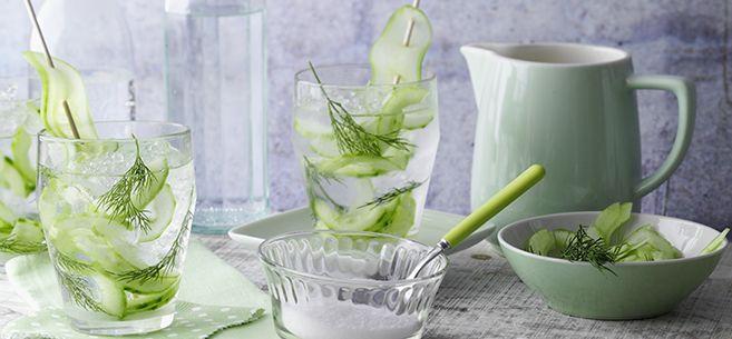 Rezept für Gurken-Gin-Drink mit Dill: 1. Salatgurke dünn schälen, längs halbieren und entkernen. Für die Garnitur 4 lange Scheiben mit einem Sparschäler dünn abschälen und beiseite legen. 2. Übrige Gurke in feine Scheiben schneiden und in eine Karaffe füllen. Weißen Rohrzucker und Gin zufügen. Dillfähnchen von den Stielen zupfen, zugeben, gut umrühren und ca. 30 Minuten kühl stellen.3. Vor dem Servieren die vier langen Gurkenscheiben auf vier Holzspieße stecken. Gläser mit Gurken-Gin-Ansatz…