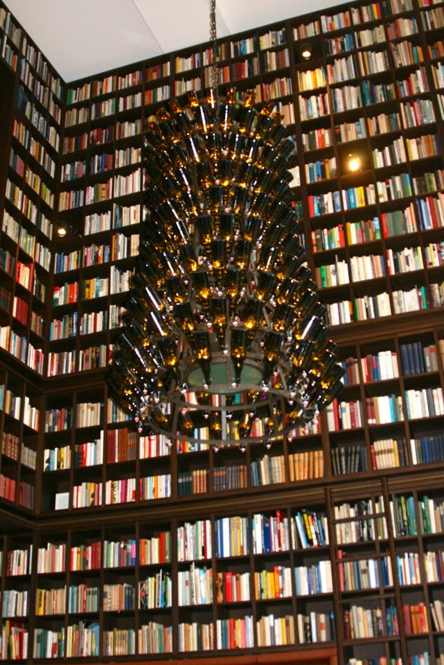 Swanky Library Hotel, Zurich, Switzerland - PointsandTravel.com Just beyond the spacious lobby was the massive 33,000-book Library Lounge that had captured me before while flipping thru their photographs on the website. These books fill three walls of the 36-foot tall lounge. All 33,000 were purchased from the same man, his life's collection. Hanging from the extensive ceiling were lighted, upside-down green beer bottle chandeliers.