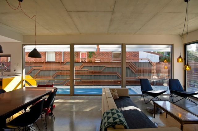 Окна, или точнее остекленная стена, гостиной выходят на забор, что не удивительно для узкого участка. Поэтому дизайнеры сделали забор украшением гостиной. .