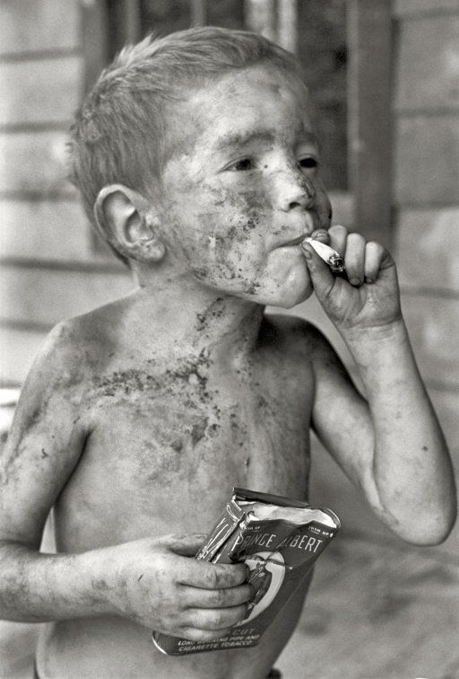 """Leatherwood, Kentucky, 1964. """"Boy covered by dirt smoking cigarette with one hand, holding can of tobacco in other."""" The tobacco-loving Cornett boys started early. Gedney Photographs Collection, Duke University."""
