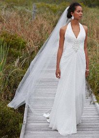 Long, soft and luxurious, elegant is an understatement in this exquisite sheath wedding dress. Chiffon halter gown features ornate beaded applique at center waist for an alluring focal point.