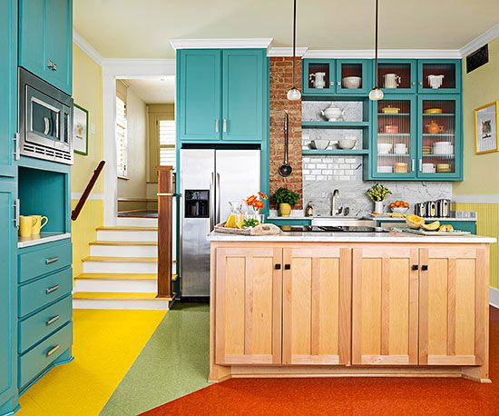 A maple island provides relief from the vibrant hues in this kitchen. Colorful vinyl flooring in an interesting pattern gives the kitchen a vintage vibe, while turquoise cabinetry provides most of the color in the room. A Car