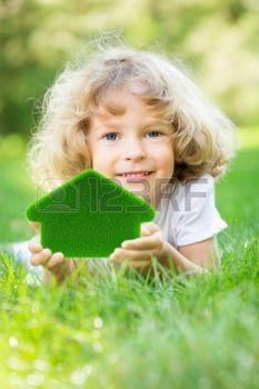 MANI CASA: Felice bambino in possesso di casa erba verde in mani Concetto di ecologia