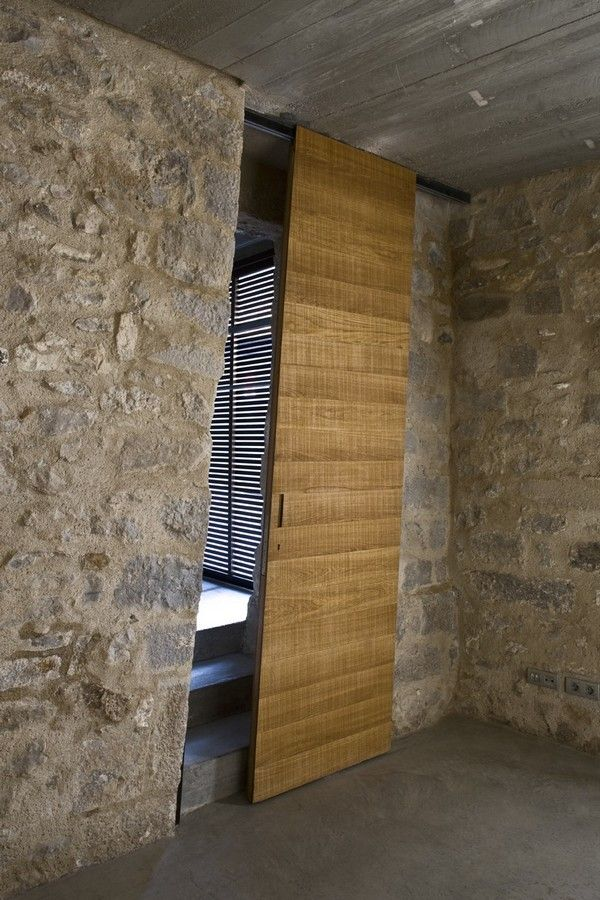 Door in Medieval Building Turned Into Contemporary Living Space. Located in the core part of Girona's medieval quarter and overlooking the Plaça de Sant Domènec, Spain.