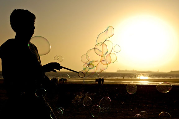 bubble boy surrounded by the bubbles of his own making - Karachi beach