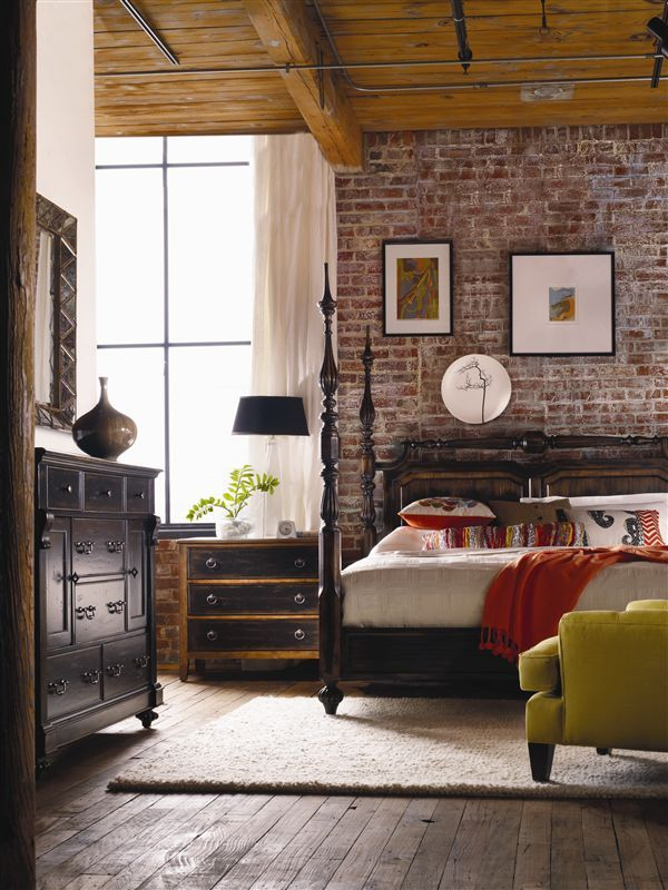 Dark wood furniture and exposed brick walls and ceiling beams. Bedroom.