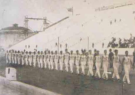 Ολυμπιακοί Αγώνες τού 1896. Η ομάδα του Πανελληνίου Γυμναστικού Συλλόγου, εισέρχεται στο Καλλιμάρμαρο Παναθηναϊκό Στάδιο [Το Στάδιο] για να αγωνισθεί.
