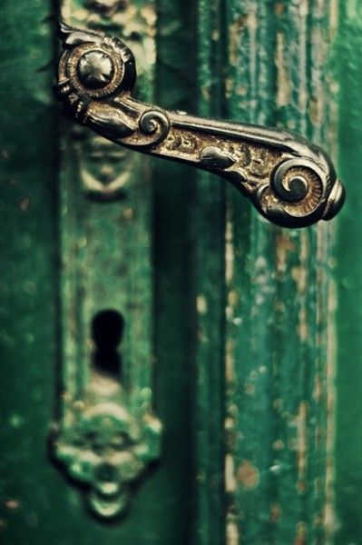 This example of depth of field photography adds balance and characteristic with a chipped green door as the blurry scenery behind the antique door handle
