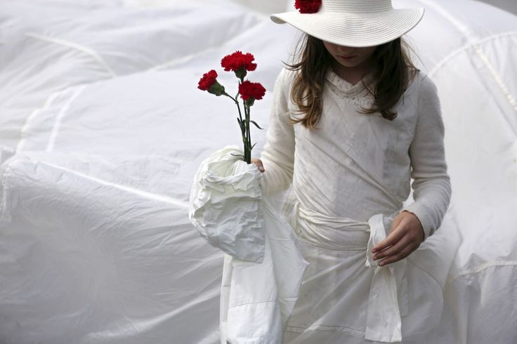 A girl carries red carnations in a parade celebrating the April 25 1974 revolution, also known as the Revolution of the Carnations, in Portugal. (AP Photo/Armando Franca)