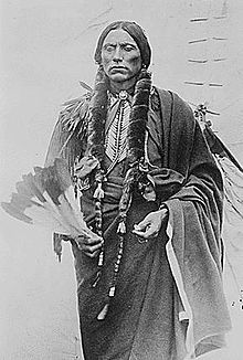 Quanah Parker, the last major chief of the Comanche Indians clasping a peyote feather fan.