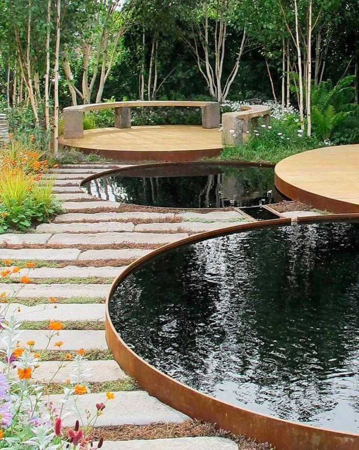 Runde spejlbassiner er klassikere, men er brugt på en ny måde i denne showhave. I stedet for et enkelt bassin, er der placeret to ved siden af hinanden i forskellige niveauer. De har jernkanter, får tilført vand fra en tagrende og er forbundet med en pumpe, der recirkulerer vandet. Hele havedesignet er baseret på cirkler – fra de runde træterrasser til de specialstøbte bænke i beton.