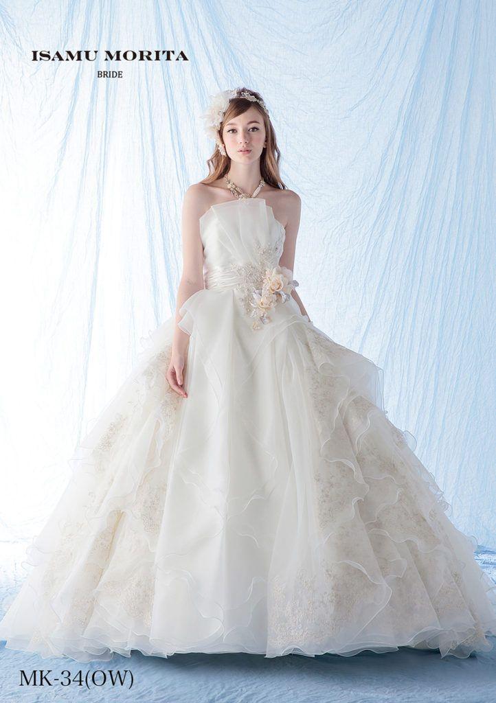 MK-34 - ISAMU MORITA ウエディングドレス - ウエストラインにフリンジで切り替えを入れて柔らかなボリュームを出しています。胸元はアシンメトリーなタッキングで形作られ、気になる部分を上手にカバーしてくれるドレスです。またビジューレースとアンティークなお花がより一層ドレスを上品にまとめました。 柔らかな素材でのバックトレーンの広がりも優雅な1着です。セットの