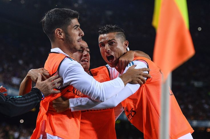 Real Madrid's forward Marco Asensio (L), Real Madrid's forward Lucas Vazquez and Real Madrid's Portuguese forward Cristiano Ronaldo (R) celebrate Barcelona's own goal during the first leg of the Spanish Supercup football match between FC Barcelona and Real Madrid CF at the Camp Nou stadium in Barcelona on August 13, 2017.  / AFP PHOTO / Josep LAGO