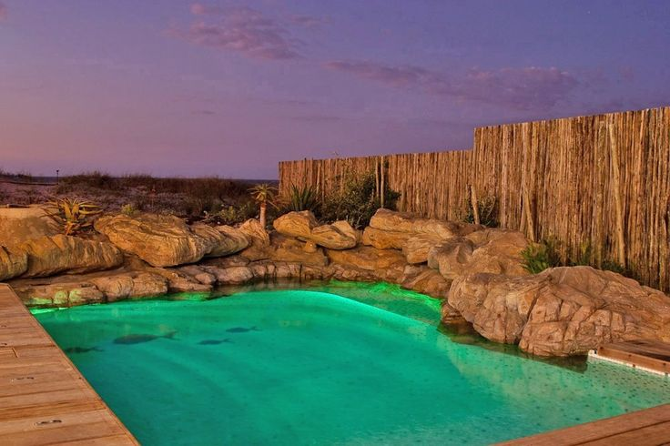 Seaside swimming pool and rock feature. Natural rock replication. Mosaic lined pool.