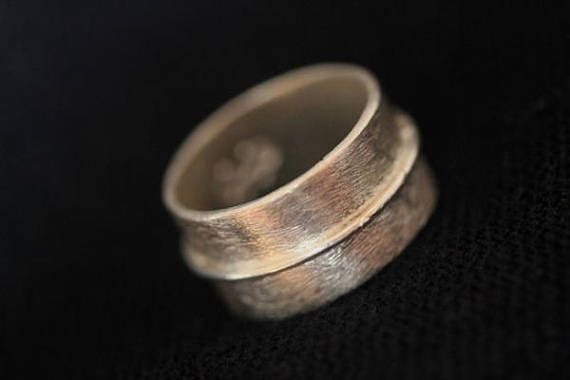 We made this ring from a 1 cm wide silver strip, soldered invisibly into final shape, ans then applied the thin silver wire to the base of the ring in the middle of the cylinder. On the inside of the ring we stamper our company logo Stories. The ring is very simple and modern,