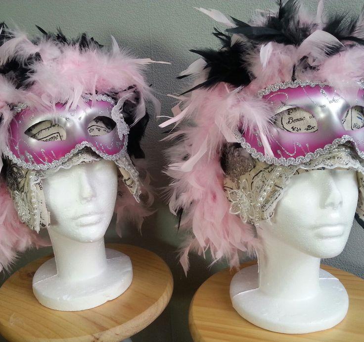 Twee fantasie Feest pruiken in de tinten roze en zwarte met witte bloem en venetiaans masker decoratie