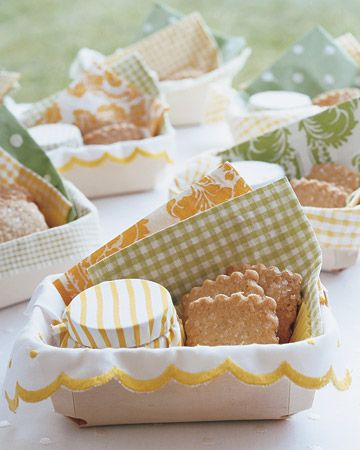 Tiny wooden favor baskets filled with a jar of lemon marmalade and a few rich, buttery shortbread cookies