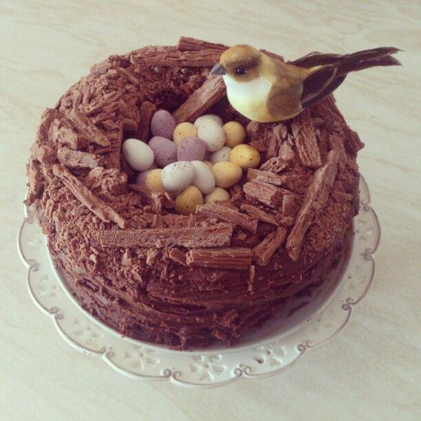 """Chocolate Easter cake.  Make any chocolate cake recipe you like and bake in two sandwich tins. Cut a hole in one of the cakes. Spread frosting on the whole half and then add the other half with the hole in on top. Then cover the whole thing with chocolate frosting. (butter, icing sugar in equal amounts, cocoa powder and melted chocolate to desired taste) add crumbled Cadbury Flake on top to create """"nest"""" and fill the hole with Mini Eggs. I bought the bird from a florist. Voila!"""