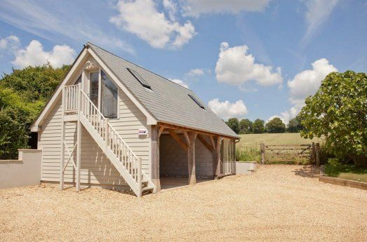 Oak outbuilding containing parking and studio above, a perfect compliment to the oak framed house just across the driveway. By Roderick James Architects.