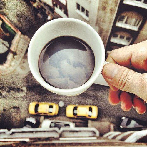 A simple photo taken over the edge of a balcony, showing the sky through the cup of coffee! A great photo!