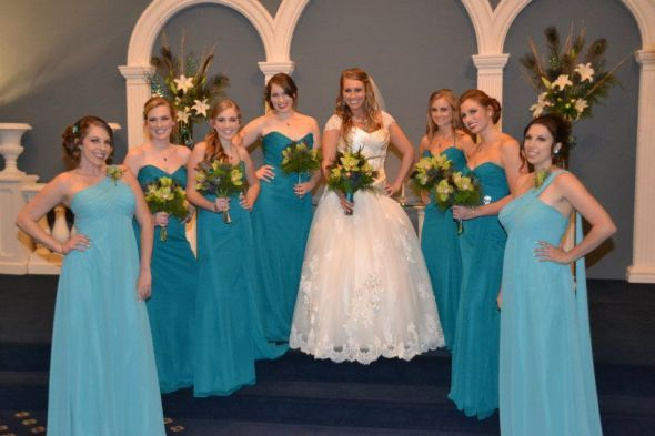 "The bridesmaids are wearing an Eden Bridals gown in ""Oasis"" and the honorary bridesmaids have Bill Levkoff gowns in ""Glacier"""