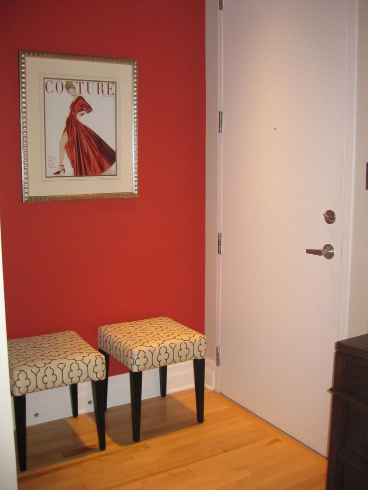 This tiny condo entrance steels all your attention with it's melon red wall, couture art and patterned square benches.