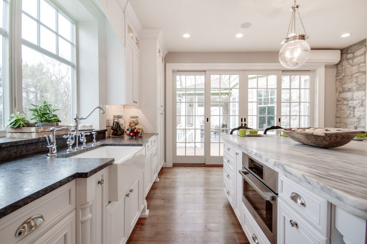 This bright white kitchen features a Mont Blanc honed quartzite island countertop with a Silver Pearl Leathered granite countertop perimeter. The backsplash has New Calacatta marble subway tile. Kitchen by Stoneshop from Cherry Hill, NJ.