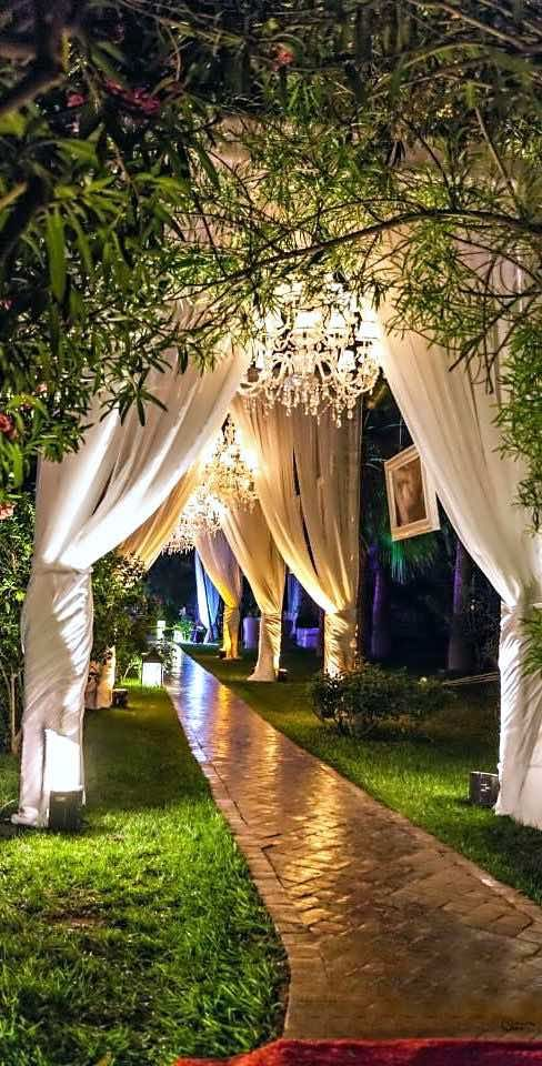Dreamy and romantic wedding decor.   Chandeliers, cortinas y flores colgantes sobre el camino central hacen de los jardines para bodas un cuento de hadas.